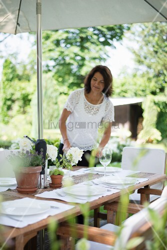 Woman decorating a set table in garden