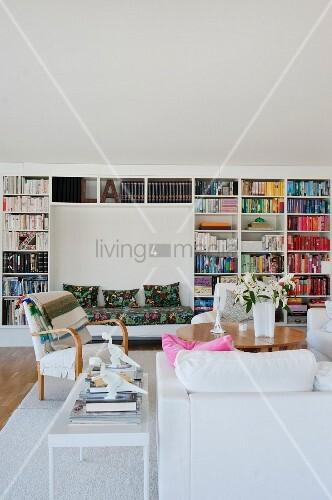 Blick über weisses Polstersofa auf Sessel und Tisch, im Hintergrund Bücherwand mit eingebauter Bank in Nische