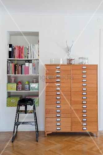 Tall chest of drawers made of pale wood next to bookshelves in niche