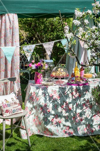 Garden buffet in sunshine on floral tablecloth below pavilion decorated with bunting