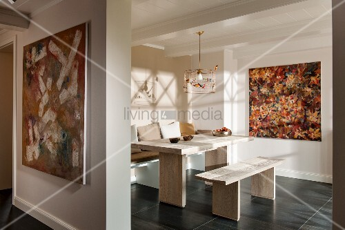 Foyer with wide open doorway and view of modern table and bench set in pale wood in front of modern artwork on wall