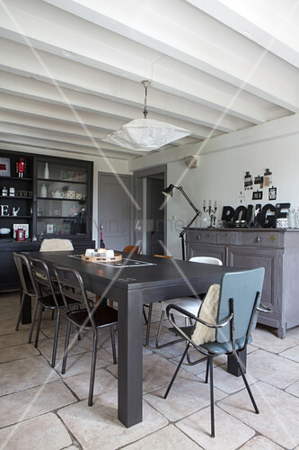 Various retro chairs around dining table in restored period apartment with white wood-beamed ceiling