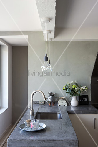Concrete worksurface with integrated sink and pendant lamps in restored period building