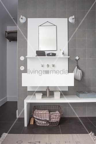 Washstand with white shelf against grey-tiled wall