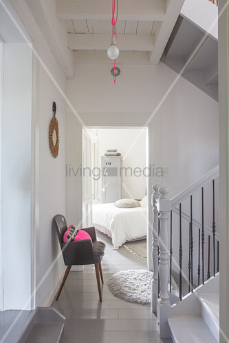 Grey chair in stairwell and view of bed through open interior door in restored interior