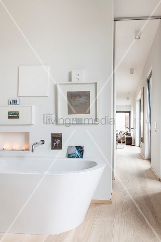 Free-standing bathtub below gallery of pictures and view into living room
