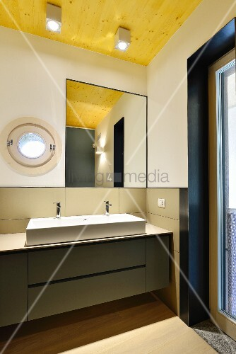 Minimalist designer bathroom with porthole window and wooden ceiling