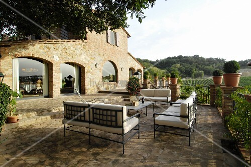 Metal furniture on Mediterranean terrace outside stone house