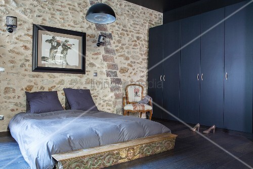 Grey-blue bed linen on double bed against stone wall next to dark blue wardrobes