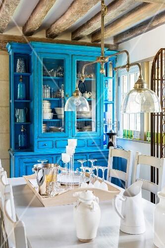 Blick über Esstisch unter Vintage Pendelleuchte auf blau lackierten Vitrinenschrank in rustikalem Esszimmer