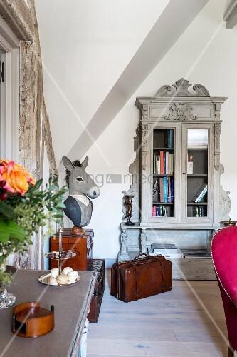 Zimmerecke in ausgebautem Dachgeschoss mit antikem grauem Vitrinenschrank und Kunstobjekt mit Eselkopf