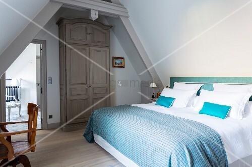 Doppelbett mit blau karierter Tagesdecke und weisser Bettwäsche im Dachgeschoss