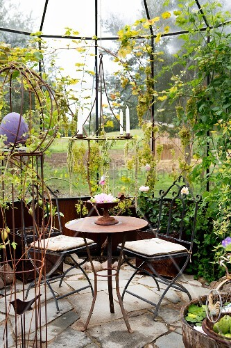 Spindly metal chairs around vintage table on stone floor in vintage-style orangery
