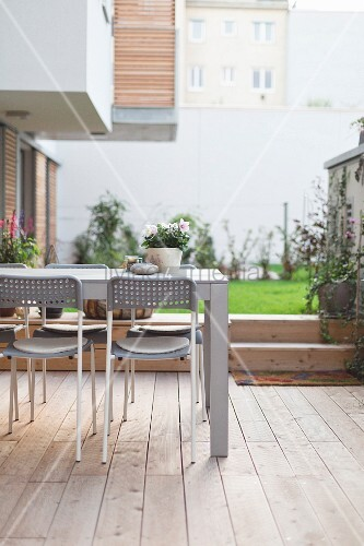 Table and chairs on wooden deck in courtyard
