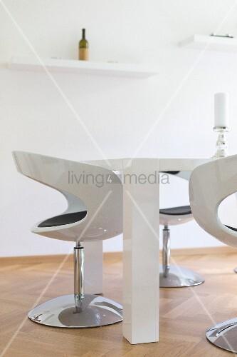 Modernes weißes Esszimmer mit Hochglanz Schalenstühlen und Blocktisch