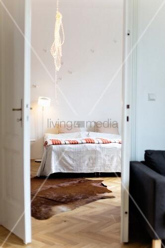 Blick ins Schlafzimmer mit Kuhfellteppich und Lichtschlauch
