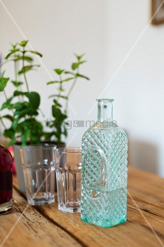 Glass bottle with structured surface used as water carafe on table