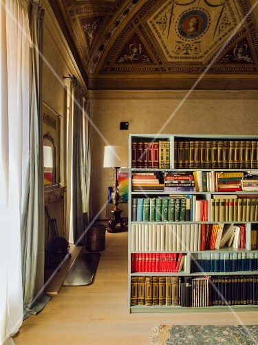 High painted ceiling and bookcase used as partition in living room of palazzo