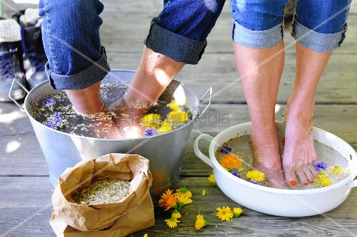 Couple bathing feet in water and medicinal flowers