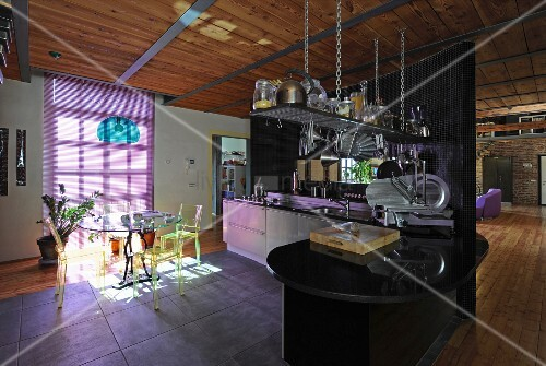 Transparent plastic chairs around dining table and purple blinds in open-plan kitchen of industrial-style loft apartment