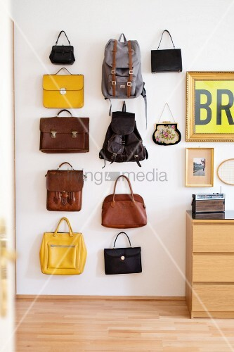 Various bags and backpacks hung in arrangement on wall