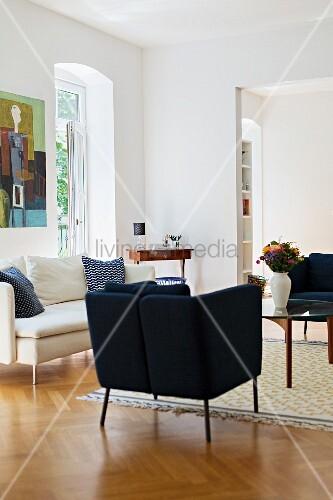 Dunkelblaue Sessel und weißes Sofa im Wohnzimmer mit Fischgrätparkett