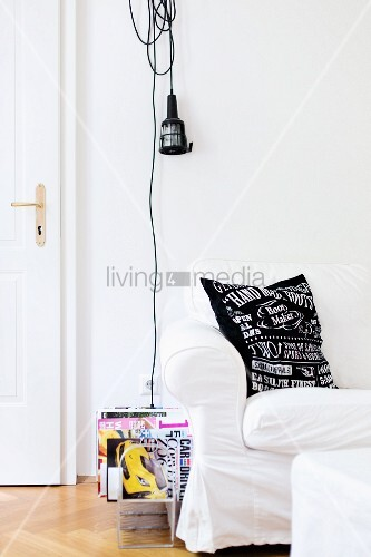 White loose-covered sofa and magazine rack below work lamp hung on wall
