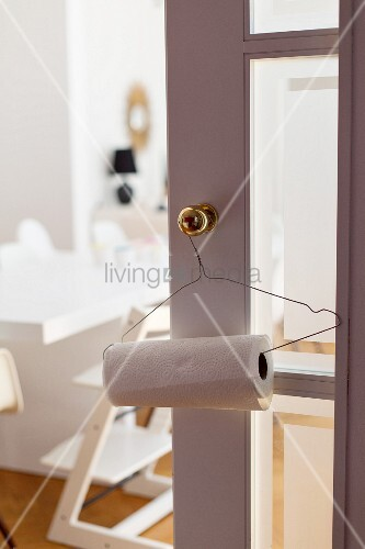 Drahtbügel mit Küchenrolle an Messingtürknopf aufgehängt