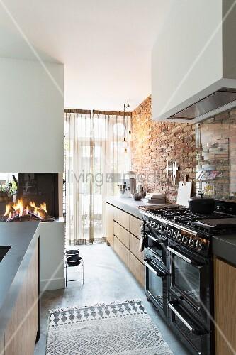 Moderne Küche mit nostalgischem Herd und Backsteinwand