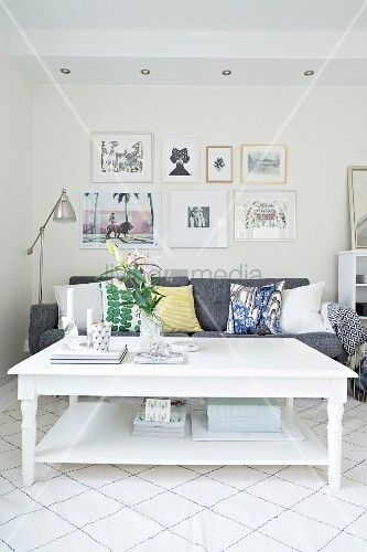 White rustic coffee table in front of grey sofa with scatter cushions below gallery of pictures