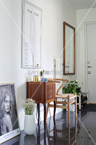 Antique cabinet and classic chair against wall of hallway with black glossy tiled floor