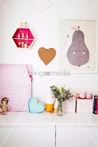Spielzeug und Bilder auf einem Sideboard im Kinderzimmer