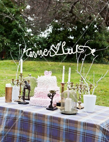 Crocheted wire lettering hung between painted branched and wedding cake on table set for wedding