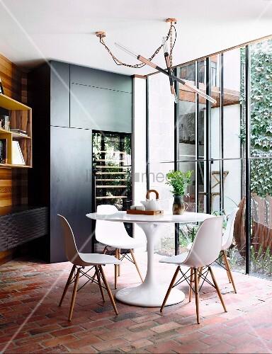 Runder Esstisch auf einem Ziegelsteinboden vor einer großen Fensterfront