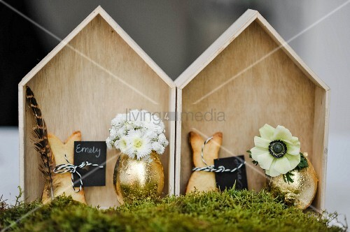 Shortbread rabbits and gilt eggs used as vases in small, chip wood houses