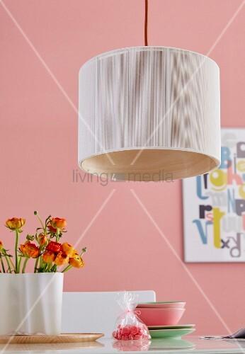 Pendelleuchte mit hellem Stoffschirm über gebogenem Holzfurnierring, über Tisch mit Ranunkeln vor rosa getönter Wand