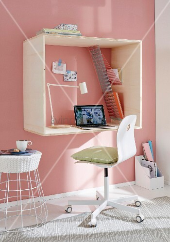 A homemade mini office on a pink wall – A wooden frame with an integrated desk and storage space made from taut ropes