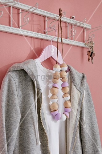 A homemade necklace of wooden beads, some painted, hanging on an old-fashioned coat rack