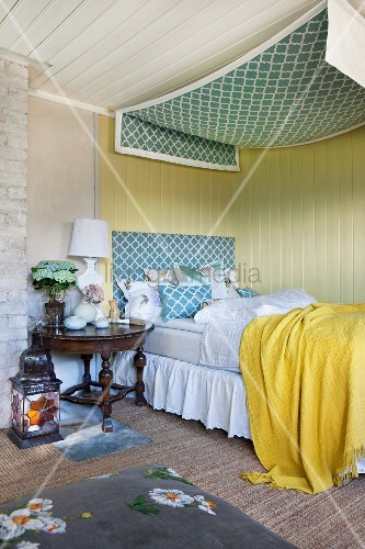 Bed with valance and canopy against yellow board wall