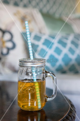 Yellow drink in mason jar with handle and drinking straw