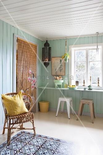 Board walls, bead curtain and breakfast bar in Bohemian kitchen