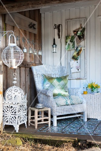 Wicker armchair on cosy terrace with board wall