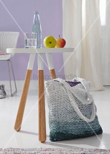 Einkaufstasche aus Stoffstreifen gehäkelt mit Farbverlauf neben Hocker im Dip-Dye Style
