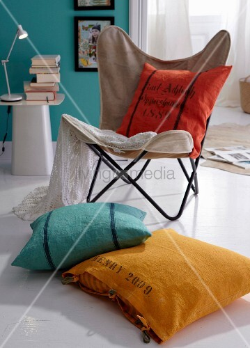 Colourful cushions on butterfly armchair and on the floor