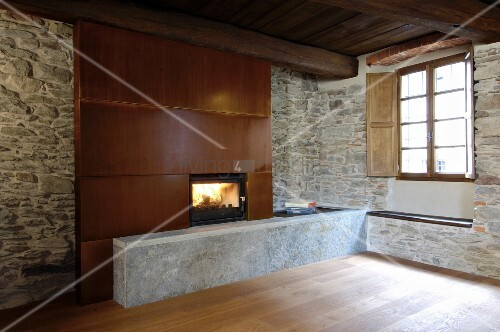 Fireplace with metal chimney break in rustic stone wall