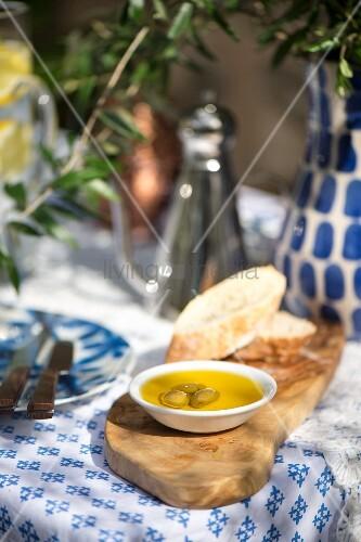 Holzbrett mit Brot, Öl und Oliven auf mediterran gedecktem Tisch