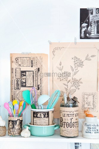 Glass jars covered in vintage-style printed paper holding kitchen utensils
