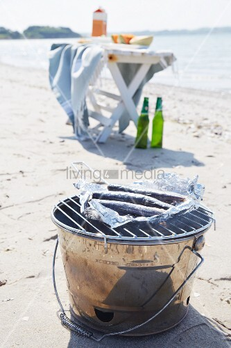 Bucket barbecue and folding table on beach