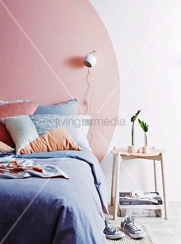 Modernes Schlafzimmer mit an die Wand gemaltem rosafarbenem Kreis als Betthaupt