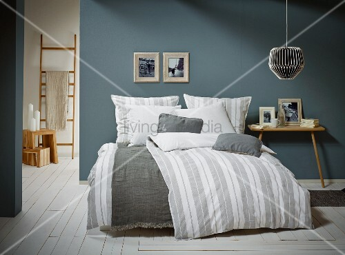 Striped bed linen and two-legged bedside table in Scandinavian bedroom